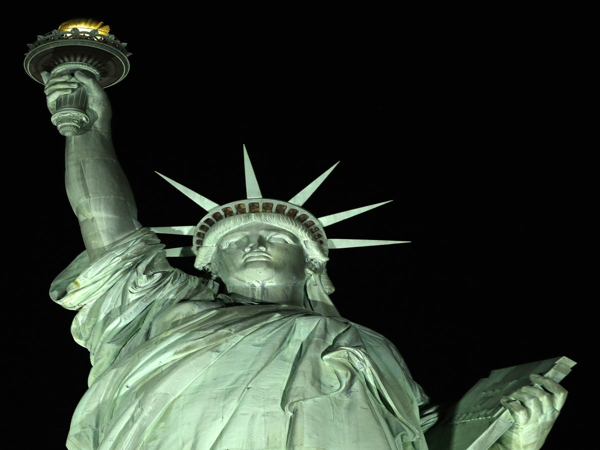Heroes Put  Refugees Welcome  Banner On The Statue Of Liberty