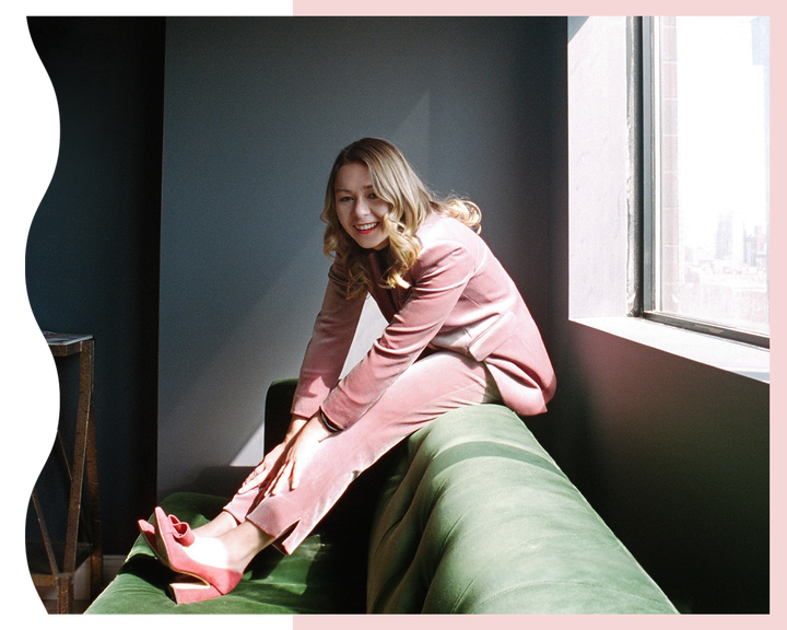 Polly Rodriguez in a pink velvet suit on a green velvet couch smiling.