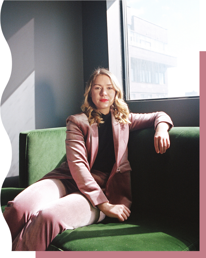 Portrait of Polly Rodriguez in a pink velvet suit on a green velvet couch.